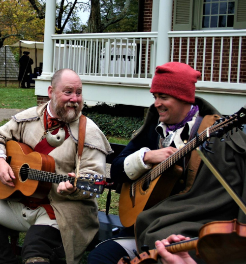 Two musicians in 18th century clothing play guitars in front of a brick historic house