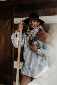 A black man in 19th century clothing looks at the camera while holding a stoneware jug in a period distillery.