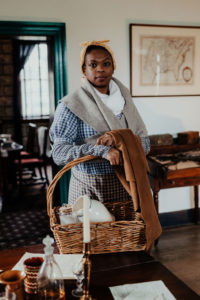 A Black woman wearing 19th century clothing and holding a basket looks at the camera in a 19th century office.
